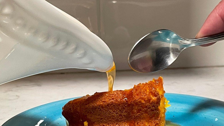 syrup being poured on orange cream cake slice